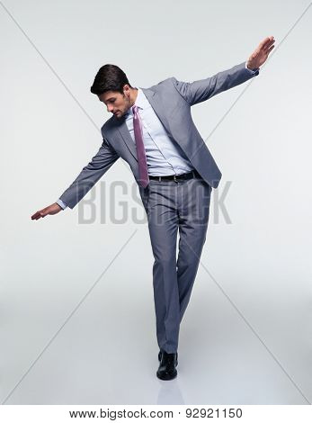 Businessman flying over gray background and looking down