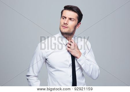 Pensive businessman straightening his tie over gray background. Looking away