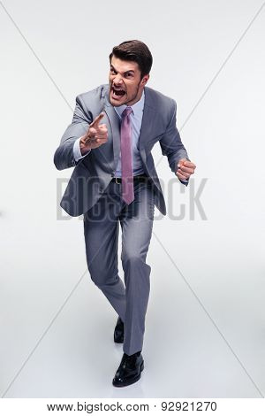 Full length portrait of angry businessman screaming over gray background