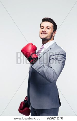 Smiling businessman in boxing gloves over gray background. Looking at camera