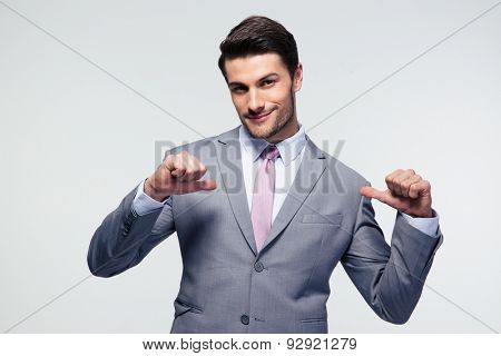 Happy businessman pointing at herself over gray background. Looking at camera