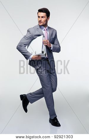 Full length portrait of a businessman running with folders over gray background. Looking away