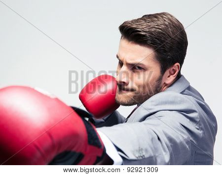 Businessman in boxing gloves hitting at camera over gray background