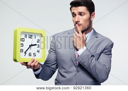 Pensive businessman holding clock over gray background