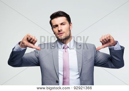 handsome businessman pointing at herself over gray background. Looking at camera