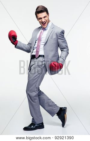 Full length portrait of a happy businessman in boxing gloves over gray background