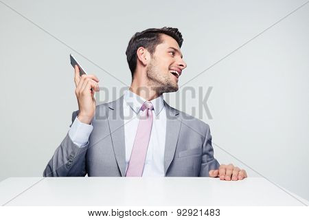 Businessman sitting at the table with smartphone and looking away over gray background