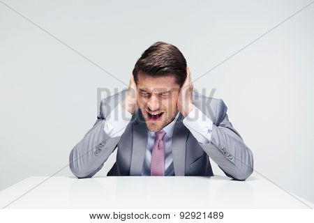 Disappointed businessman sitting at the table and covering his ears over gray background