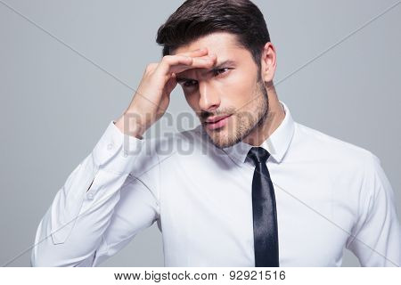 Portrait of a businessman with headache over gray background