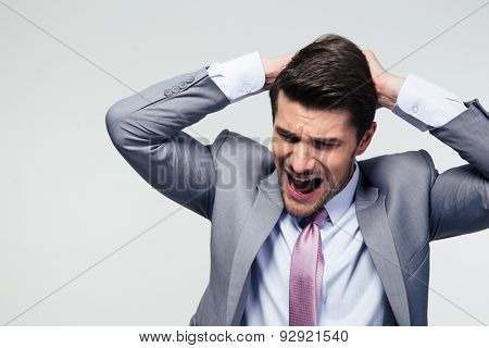 Portrait of a disappointed businessman over gray background