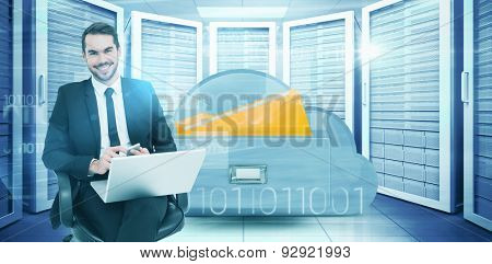 Happy businessman with laptop using smartphone against composite image of cloud computing drawer