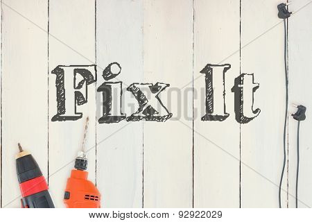 The word fix it against diy tools on wooden background