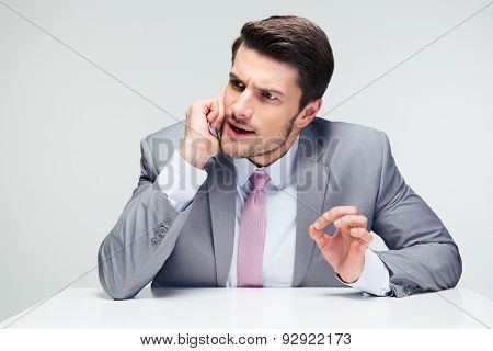 Confident businessman sitting at the table and talking on the phone over gray background