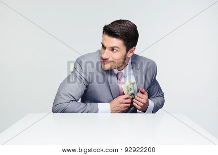 Businessman putting money in pocket over gray background and looking away