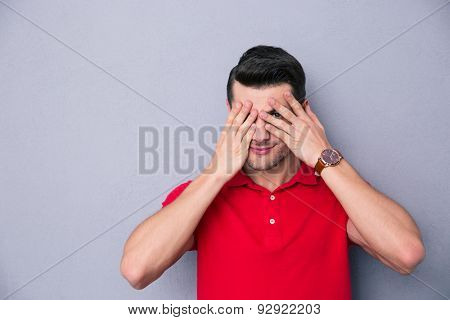 Casual man covering his eyes with fingers over gray background