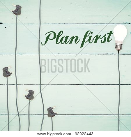 The word plan first against light bulbs on wooden background