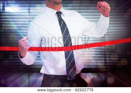 Businessman crossing the finish line against window overlooking city