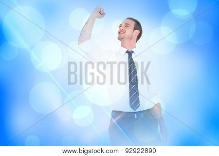 Businessman cheering with clenched fist against blue abstract light spot design