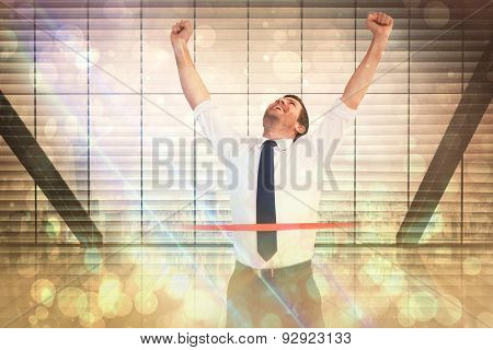 Businessman celebrating success with arms up against window overlooking city