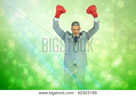 Furious businessman posing with red boxing gloves against green abstract light spot design