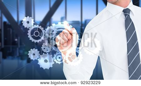 Businessman pointing with his finger against room with large window looking on city