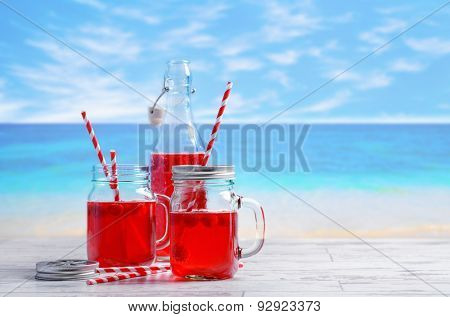 Summer fruit drinks with beach blur background