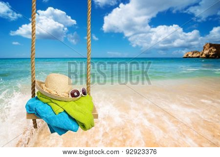 Summer rope swing with beach towels, sunhat and shades with beach blur background