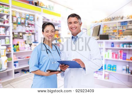 Doctor and nurse smiling at camera against close up of shelves of drugs