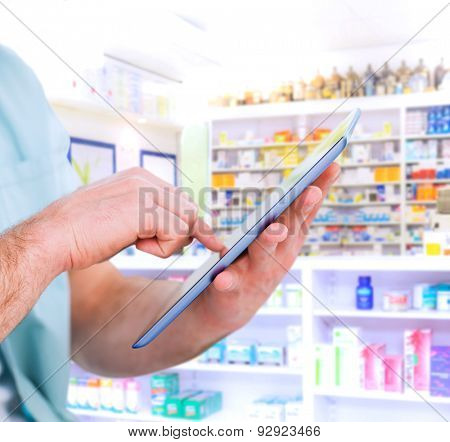 Man using tablet pc against close up of shelves of drugs