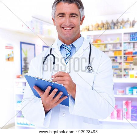 Happy doctor writing on clipboard against close up of shelves of drugs