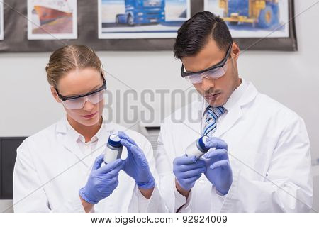 Concentrated scientists looking at medication in laboratory