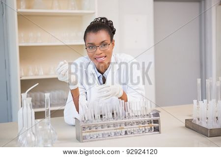Smiling scientist working with pipette in laboratory