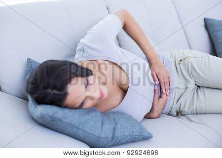 Sick brunette having stomachache in the living room