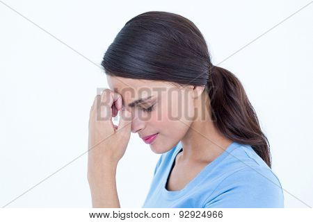 Brunette with a headache and hand on forehead on white background