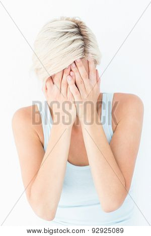 Sad blonde woman crying with head on hands on white background
