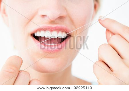 Pretty woman using dental floss on white background