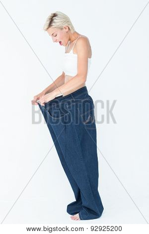 Surprised blonde wearing too large pants on white background