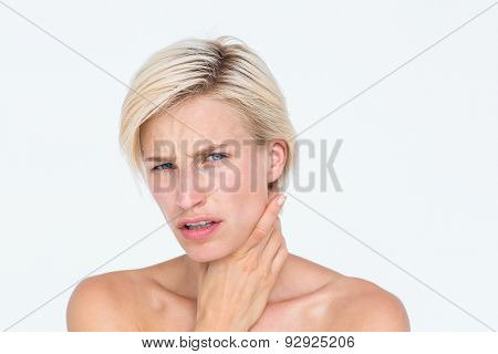 Pretty blonde suffering from throat pain on white background