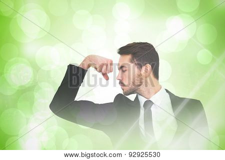 Cheerful businessman tensing arm muscle against green abstract light spot design