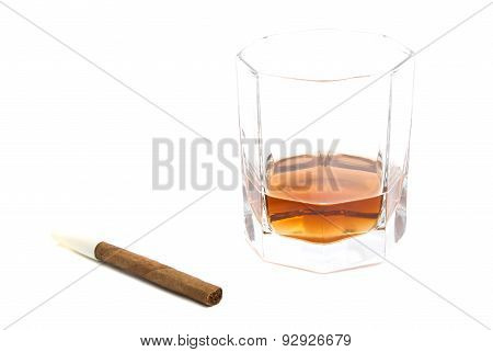 Cigarillo And Glass Of Cognac On White