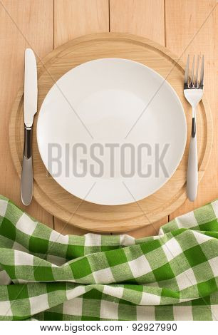 plate, knife and fork at cutting board on wooden background
