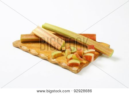 fresh cut rhubarb on wooden cutting board