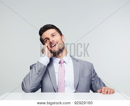Happy businessman sitting at the table and talking on the phone over gray background