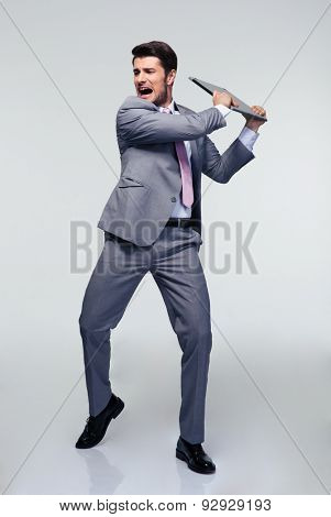 Full length portrait of angry businessman trying to smash his laptop over gray background