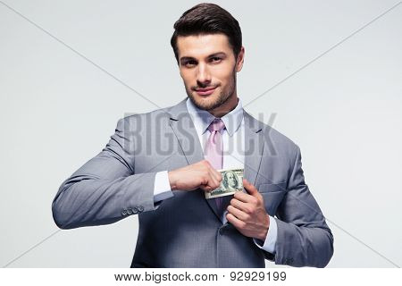 Businessman putting money in pocket over gray background. Looking at camera