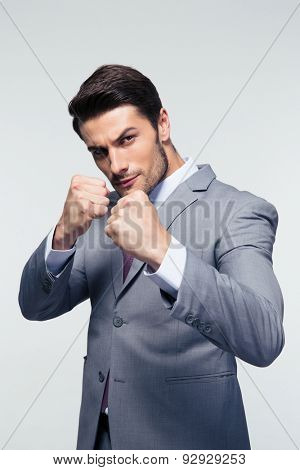 Confident businessman ready for fight over gray background. Looking at camera