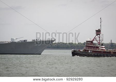 STATEN ISLAND, NY - MAY 20, 2015: The bow of the USS Stout (DDG 55) and the McAllister Sisters tugboat as the warship is guided into port at Sullivans Pier in Staten Island at the start of Fleet Week.
