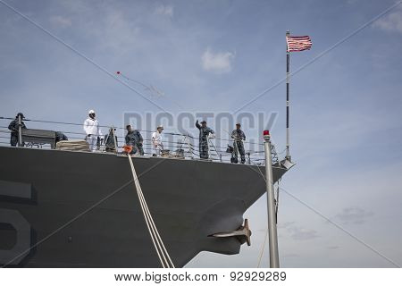 STATEN ISLAND, NY - MAY 20 2015:  A sailor from the USS Stout (DDG 55) throws a line to the port services crew as the ship docks at Sullivans Pier in Staten Island for Fleet Week NY 2015.