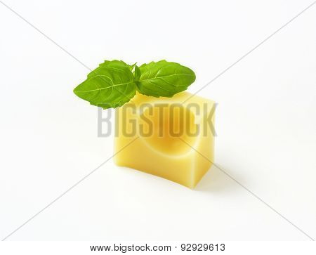 cube of fresh emmental cheese and basil on white background