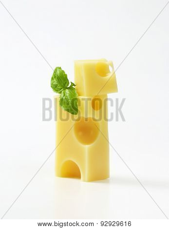 slices of fresh emmental cheese and basil on white background